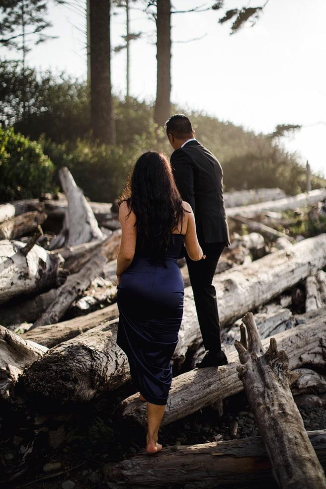Couple walking through drift wood for Ruby Beach engagement Photoshoot