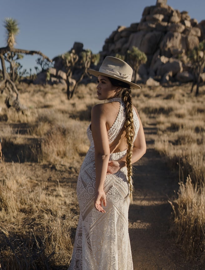 Bride in bohemian wedding dress with hat at her desert wedding in Joshua Tree National Park.