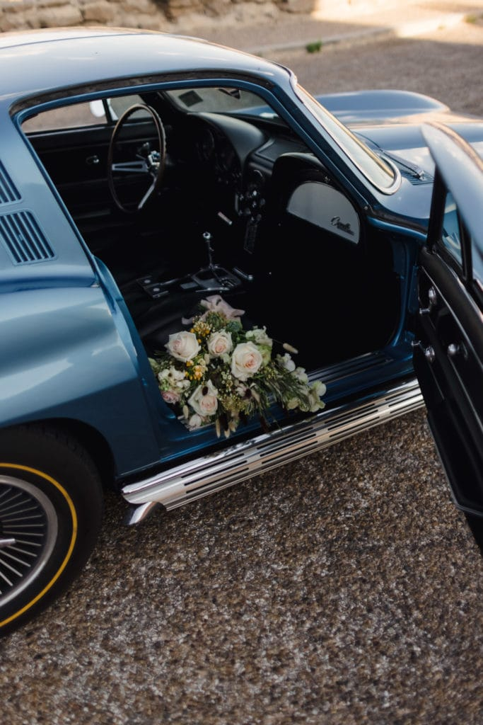 A wedding bouquet in the seat of a vintage corvette ar an elopement ceremony.